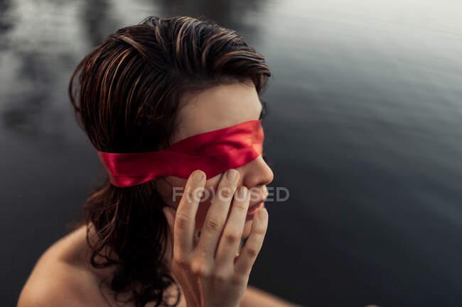 Vista lateral de turista femenina gentil anónima con los ojos vendados rojos tocando la cara contra el agua a la luz del día - foto de stock