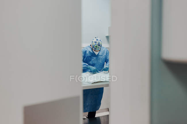 Focused male veterinarian in uniform and respiratory mask using medical instruments during surgery in hospital — Stock Photo