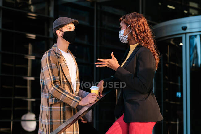 Side view of anonymous multiethnic colleagues in face masks talking while looking at each other on city street during COVID 19 pandemic — Stock Photo