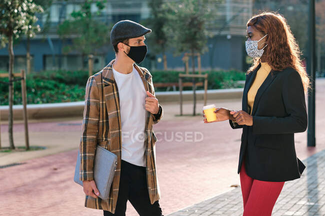 Side view of anonymous multiracial business coworkers in masks with coffee to go and laptop talking while looking at each other in town in back lit — Stock Photo