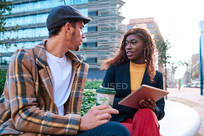 Black businesswoman with tablet speaking with male partner holding disposable glass of hot drink while looking at each other on urban bench — Stock Photo