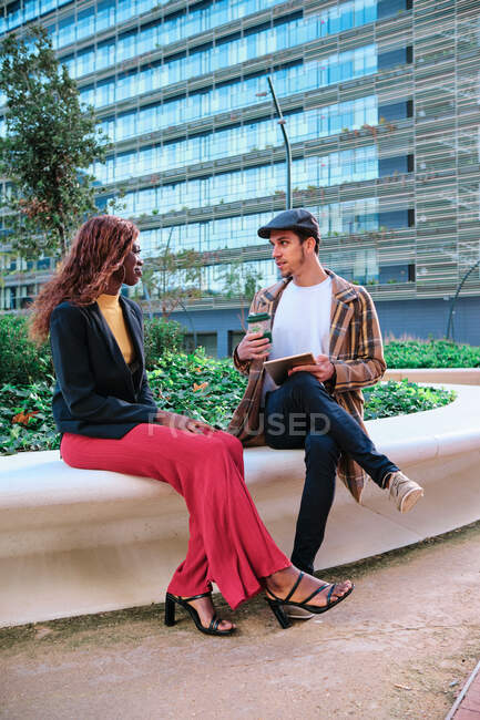 Black businesswoman speaking with male partner holding disposable glass of hot drink and tablet computer while looking at each other on urban bench — Stock Photo