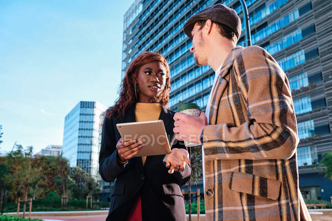 Young black businesswoman with tablet talking to male colleague with takeaway coffee while looking at each other in town — Stock Photo