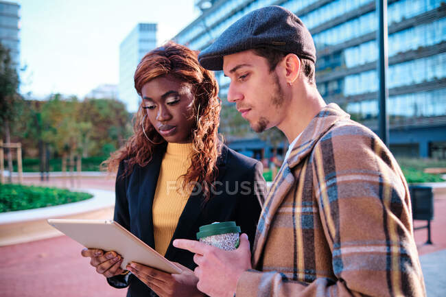 Black businesswoman with tablet speaking with male partner holding disposable glass of hot drink standing in the street — Stock Photo