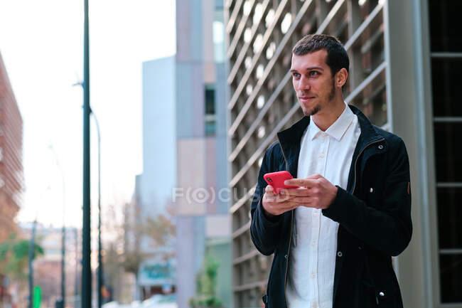 Молодой мужчина исполнительный в формальной одежде с помощью мобильного телефона, глядя в сторону в городе — стоковое фото