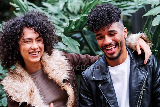 Feliz joven pareja diversa en chaquetas calientes abrazándose en el exuberante parque con sonrisas dentales - foto de stock