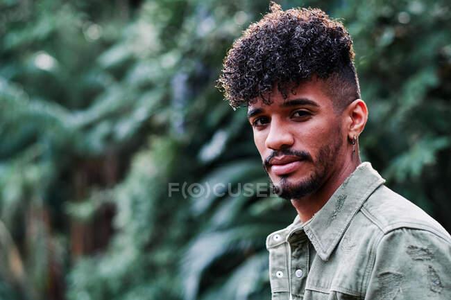 Спокойный молодой афроамериканец в повседневной одежде, стоящий в зеленом богатом парке и смотрящий в камеру — стоковое фото