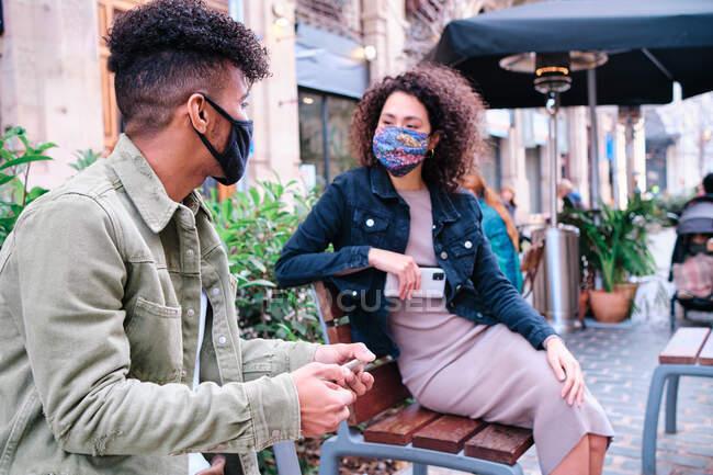 Содержание молодых этнических друзей в повседневных нарядах и защитных масках для лица, держащих современные мобильные телефоны, сидя вместе, глядя друг на друга на уличной скамейке — стоковое фото