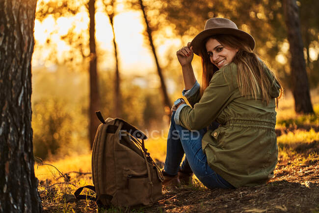 Back view full body slim female hiker wearing casual clothes with backpack sitting in green abundant woodland and admiring wonderful sunset — Stock Photo