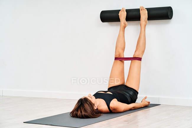 Анонимная спортсменка в спортивной одежде и браслете сопротивления прикасается к стене ногами и катком пилатеса на коврике — стоковое фото