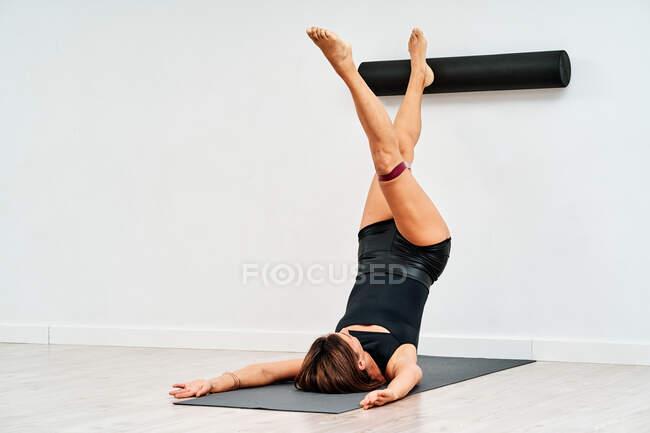 Анонимная спортсменка в спортивной одежде стоит на плечах, прикасаясь к стене ногами и катком пилатеса на коврике — стоковое фото