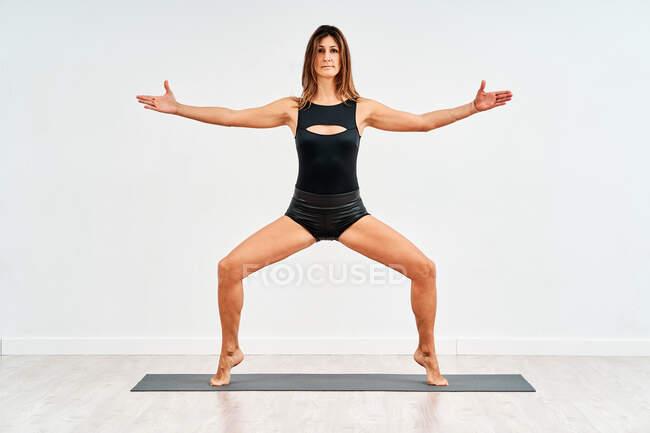 Молодая спортсменка в активной одежде стоит на цыпочках с поднятыми руками, глядя в камеру во время тренировки на белом фоне — стоковое фото