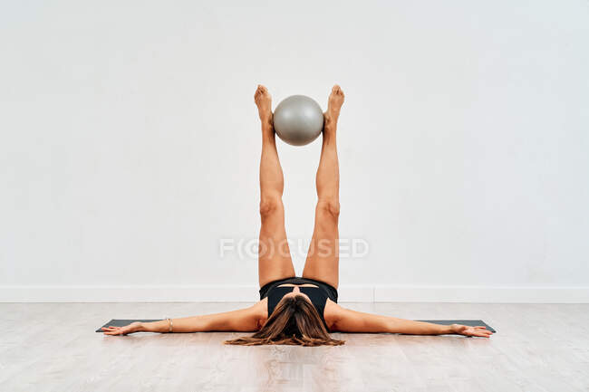 Anonymous female athlete in sportswear lying on mat with raised legs holding small fitness ball during workout in gymnasium — Stock Photo