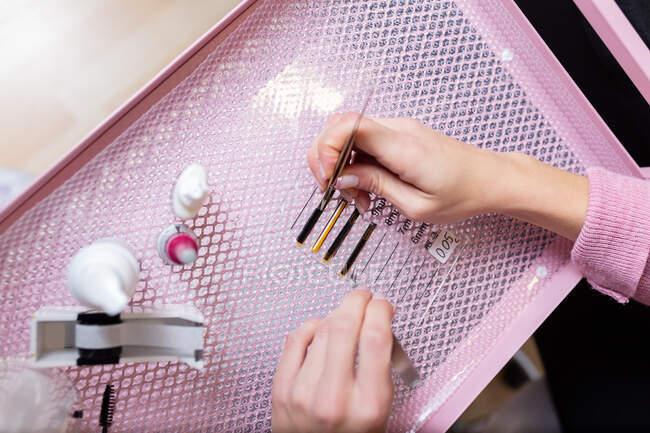 Культура зверху Анонімна жінка-косметолог з жовтцями збирає штучні вії з коробки, розміщеної на рожевому столі в сучасній студії краси. — стокове фото