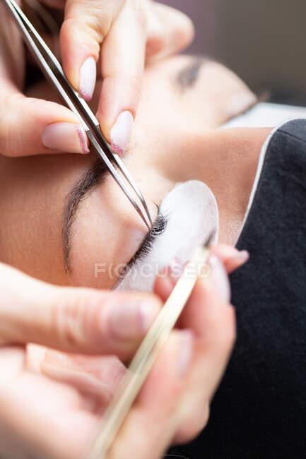 Maestro femminile professionista di coltura con pinzetta che applica ciglia artificiali su cliente femminile giovane in maschera di faccia in salone moderno leggero — Foto stock