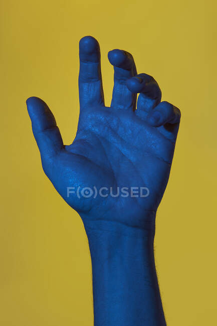Man's blue hand with open palm over yellow background. Isolated vertical photo — Stock Photo