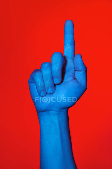Man's blue hand making the number one sign over red background. Isolated vertical photo — Stock Photo