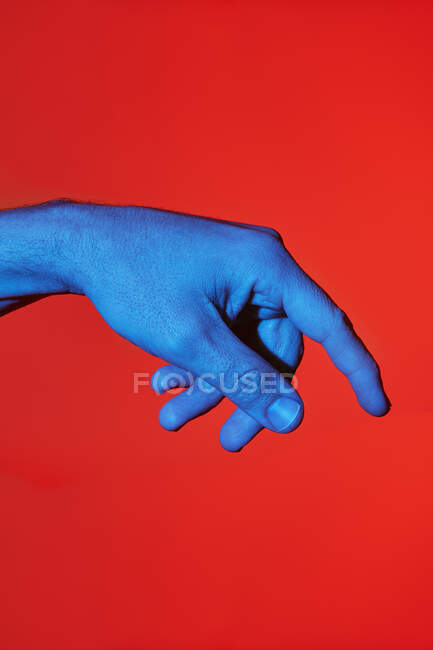 Man's blue finger pointing downwards over red background. Isolated vertical photo — Stock Photo