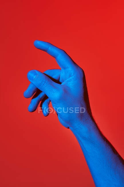 Man's blue hand pointing upwards over red background. Isolated vertical photo — Stock Photo