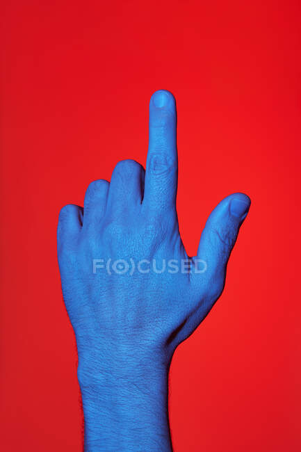 Man's blue hand pointing whit his finger over red background. Isolated vertical photo — Stock Photo
