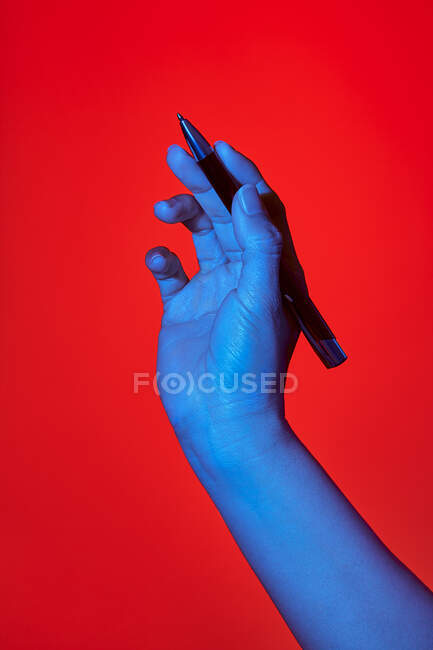 Woman's blue hand over red background, writing with a pen. Isolated vertical photo — Stock Photo