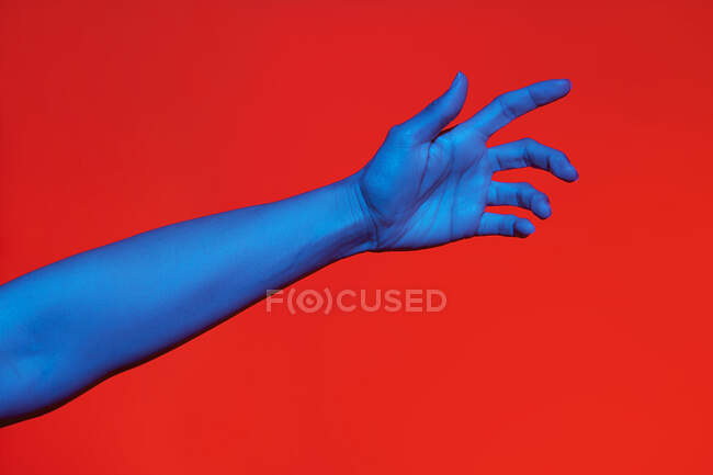 Woman's blue arm with open palm over red background. Isolated horizontal photo — Stock Photo