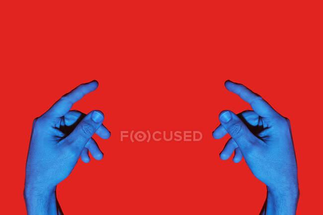 Протилежні руки чоловіків вказують один на одного на червоне тло. Ізольоване горизонтальне фото — стокове фото