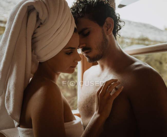 Femme tendre avec serviette enroulée autour de la tête embrassant petit ami doucement barbu avec les yeux fermés près de la fenêtre avec des gouttes d'eau dans la cabane — Photo de stock