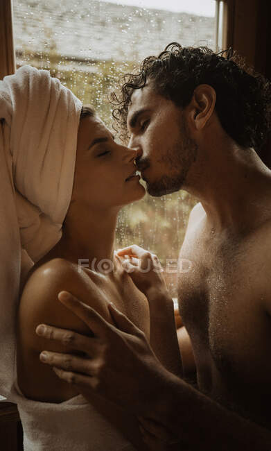 Tender woman with towel wrapped around head embracing gently bearded boyfriend with closed eyes near window with water drops in shack — Stock Photo