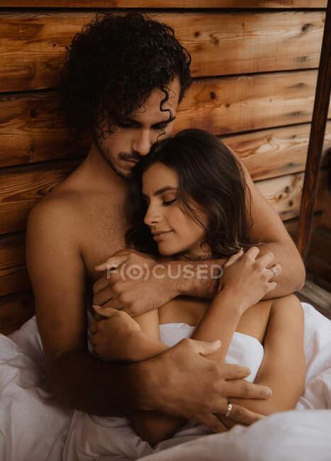 Desde arriba amante joven pareja que se une tiernamente y acostado con los ojos cerrados sobre una manta blanca y suave en la terraza de la casa de madera en el día de otoño - foto de stock