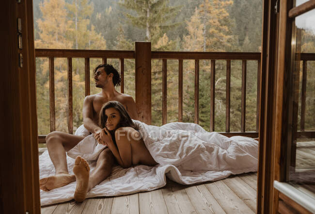 Romantic undressed couple lying on cozy blanket and cuddling on wooden cottage terrace against deciduous forest on autumn — Stock Photo
