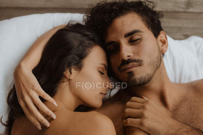 From above romantic young couple lying down sleeping with eyes closed on soft blanket — Stock Photo