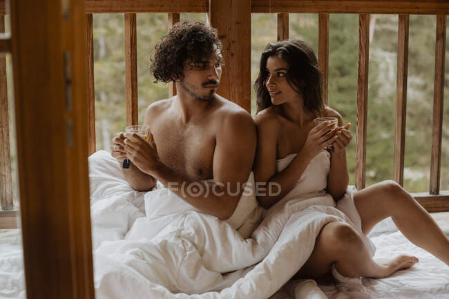 Relaxed young undressed couple covering bodies with soft blankets and sitting back to back with cups of teas on terrace on autumn day looking at each other — Stock Photo
