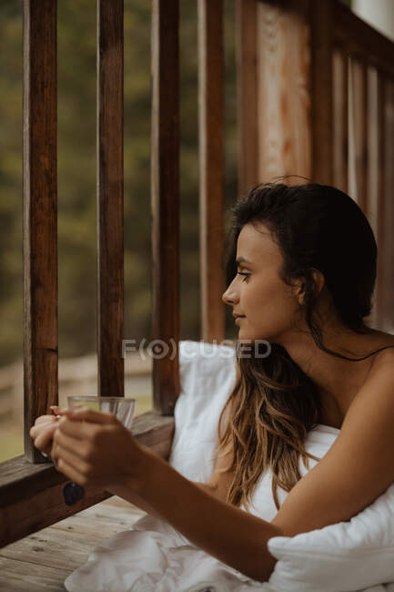 Serene young female with bare shoulder lying with cup of tea on soft blanket on wooden porch and looking away in pleasant thoughts — Stock Photo