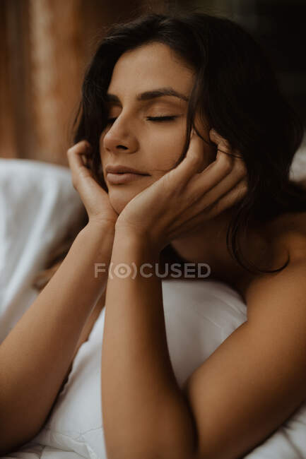 Attractive young brunette covering body with cozy blanket and touching face tenderly with eyes closed — Stock Photo