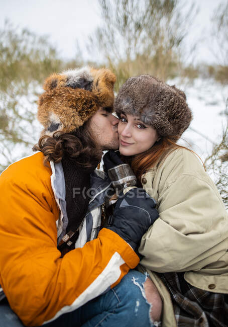 Young couple of travelers in outerwear sitting close and kissing cheek against mount while looking at camera in winter in Asturias — Stock Photo