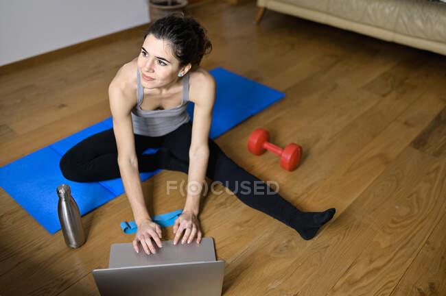 Из выше взрослого содержания женщина-спортсмен смотрит видео-учебник на ноутбуке во время тренировки на коврике в доме — стоковое фото