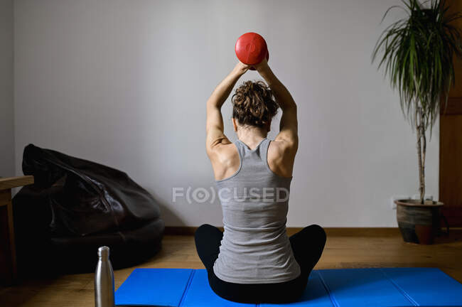 Back view of adult anonymous female athlete sitting with crossed legs and raised arms during training with dumbbell in house — Stock Photo
