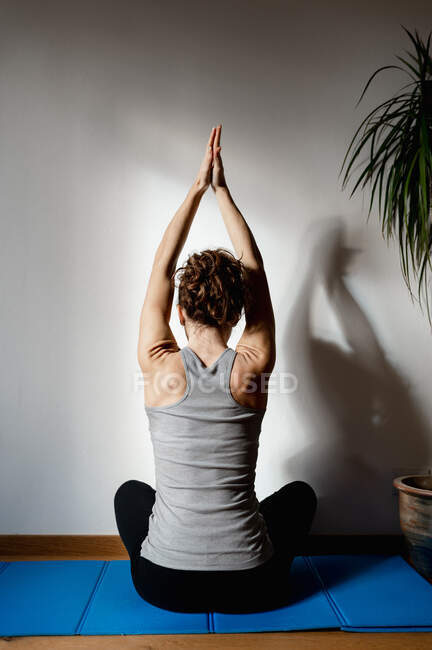 Back view of adult anonymous female athlete sitting with crossed legs and raised arms during training in house — Stock Photo