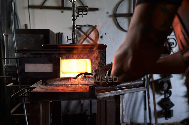 Back view of anonymous tattooed young male forger in apron heating metal in furnace while working in grungy smithy — Stock Photo