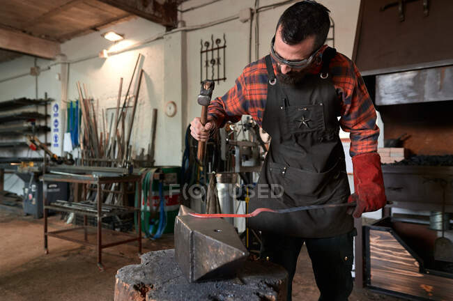Concentrated young bearded blacksmith in apron and protective goggles striking heated metal with hammer on anvil while working in forge — Stock Photo