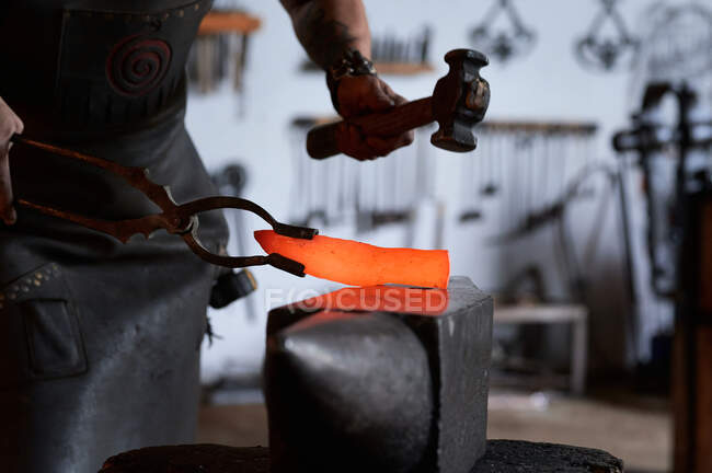 Side view of anonymous tattooed young male forger in apron heating metal in furnace while working in grungy smithy — Stock Photo
