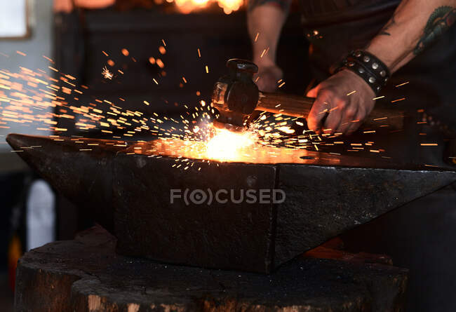 Боковой вид молодого жестокого бородатого мастера в фартуке и очках, нагревающего и ударяющего утюг на наковальне молотком во время работы в традиционной кузнице — стоковое фото
