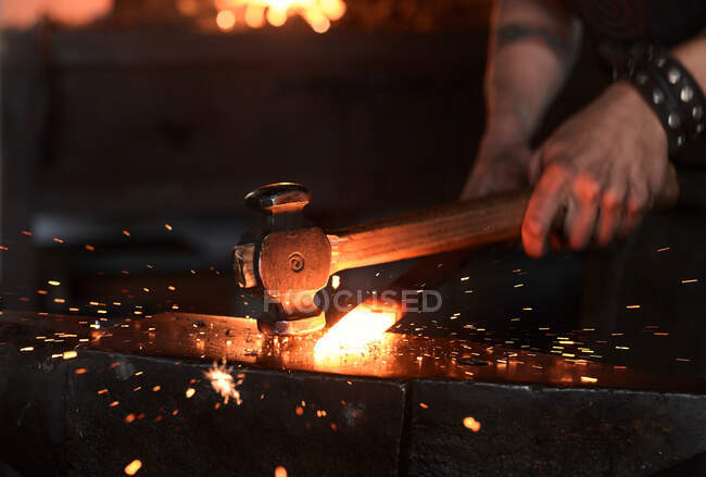 Side view of young brutal bearded craftsman in apron and goggles heating and striking iron on anvil with hammer during work in traditional smithy — Stock Photo