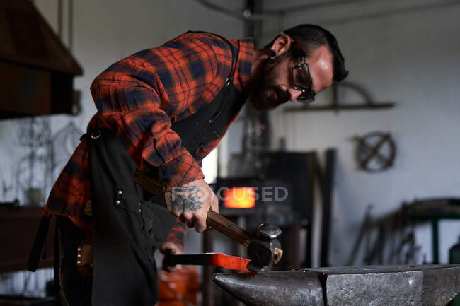 Vue latérale du jeune artisan barbu brutal en tablier et lunettes chauffant et frappant fer sur enclume avec marteau pendant le travail dans la forge traditionnelle — Photo de stock