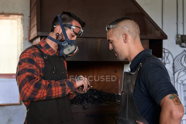 Side view of young stylish bearded blacksmith in apron and protective respirator showing metal detail to male colleague while standing near fireplace in smithy — Stock Photo