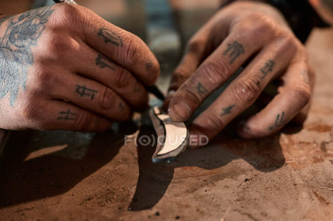 High angle of crop unrecognizable male blacksmith with tattoos on hands cutting iron detail with pointed chisel while working in smithy — Stock Photo