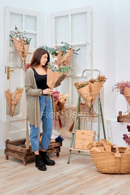 Vista lateral do cliente feminino escolhendo flores na loja — Fotografia de Stock