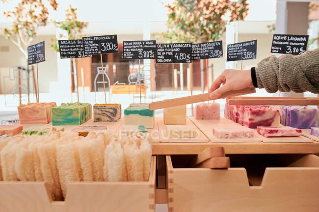 Анонимная женщина-покупатель собирает мыло из натуральных ингредиентов во время покупок в магазине экологически чистыми продуктами — стоковое фото