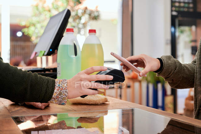 Side view of crop anonymous female client making payment with cellphone on wireless terminal for paying for detergent at counter — Stock Photo